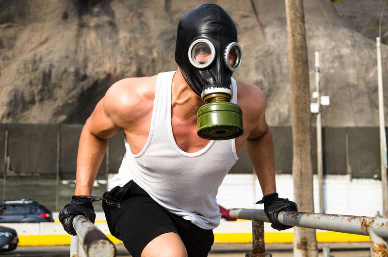 Man wearing gas mask exercising outdoors