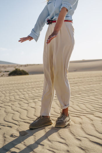 Stylish young caucasian woman standing in desert background dressed in light summer clothes. Desert Dunes Sand Landscape Arid Dry Climate Wild Hot Sandy Corralejo Natural Nature Fuerteventura Canary Islands Woman Female Girl person Young Free Freedom Background Model Posing Traveler Caucasian Evening Golden Alone Lost Wanderer Wandering Dreaming Travel Vacation Adventure Explore Tourist Summer