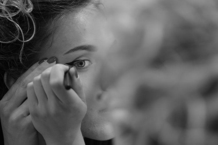 Close-up of woman applying eyeliner