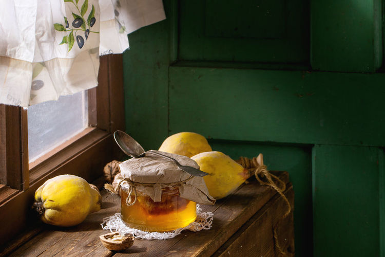 Close-up of quinces with honey on table