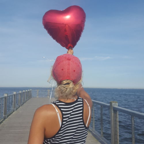Rear view of woman holding red heart shape balloon on pier over sea against sky