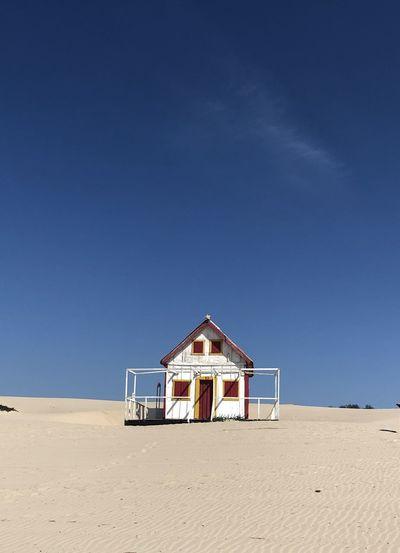 House on beach against clear blue sky