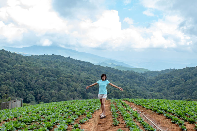 Full length of woman with arms outstretched standing on agricultural field against sky