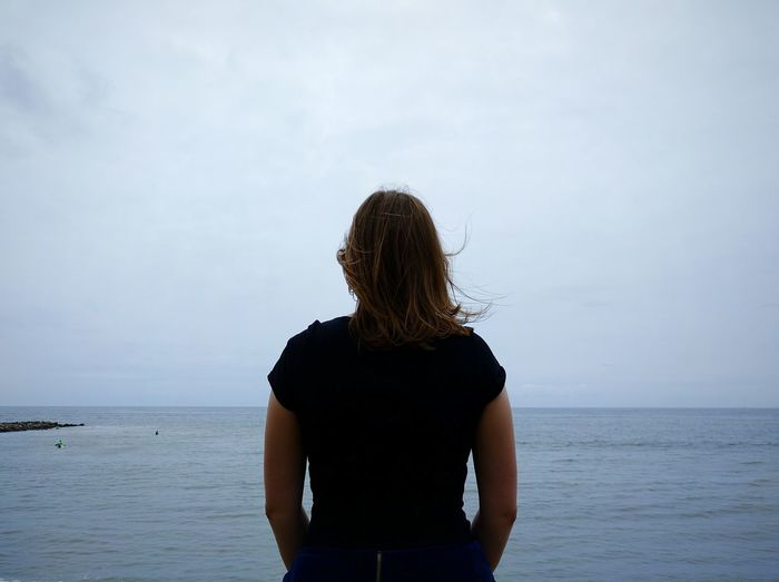 Rear View Of Woman Standing In Front Of Sea Against Sky