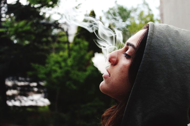 EyeEm Selects One Person Young Adult Real People Young Women Leisure Activity Headshot Focus On Foreground Outdoors Day Lifestyles Human Face Close-up Tree People Smoking Smoke The Week On EyeEm