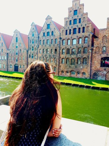 love of my Life in front of old Saltstorage River Trave Canalview Salzspeicher Lübeck Sonnig Sunny Old Buildings Green Grass Green Water Love My Girl Long Hair ARTfoxHH Water Clear Sky City Sky Architecture Building Exterior Built Structure Urban Fashion Jungle