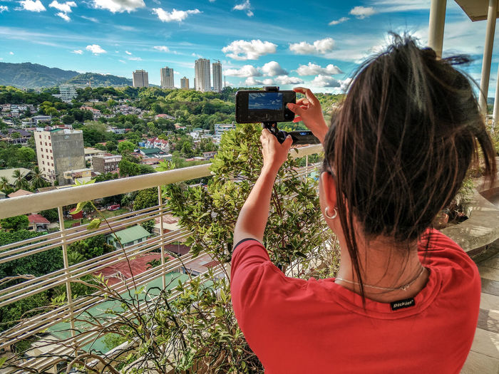 Portrait of woman photographing cityscape