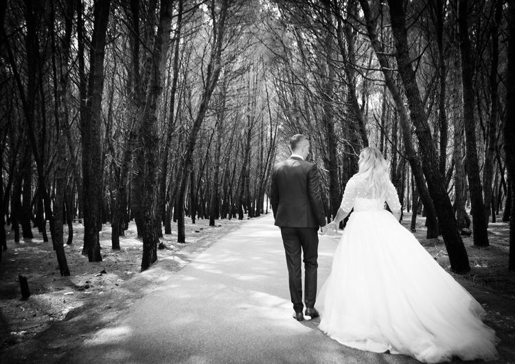Rear view of wedding couple walking on road amidst trees