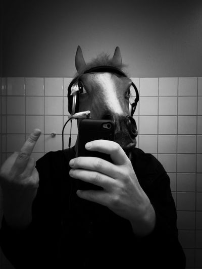 Man wearing horse mask and headphones gives middle finger