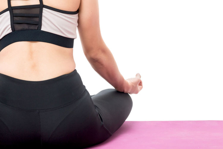 Low section of woman meditating while sitting on exercise mat against white background