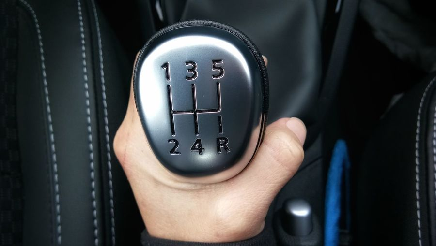 Close-up of human hand holding gearshift in car