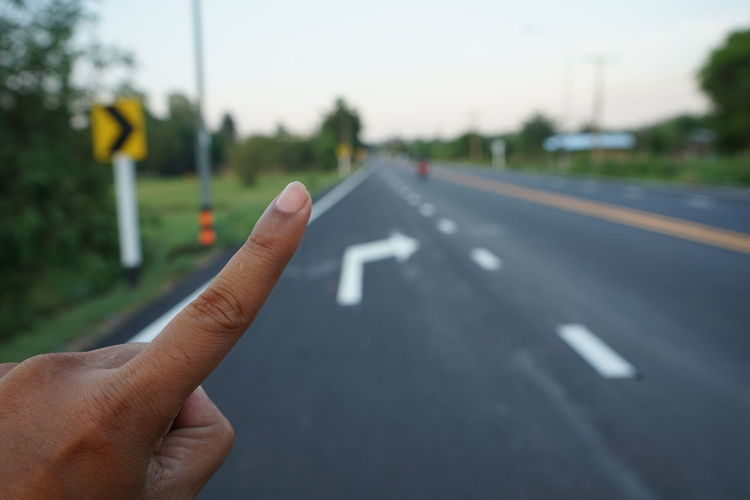 Cropped image of person hand on road against sky