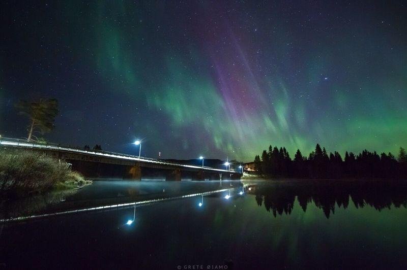 Bridge reflecting in lake against sky during aurora borealis