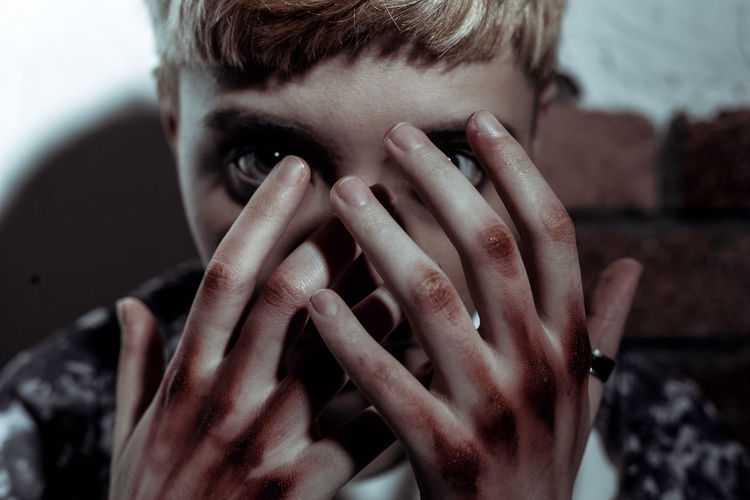 Close-up portrait of young woman with dirty hands