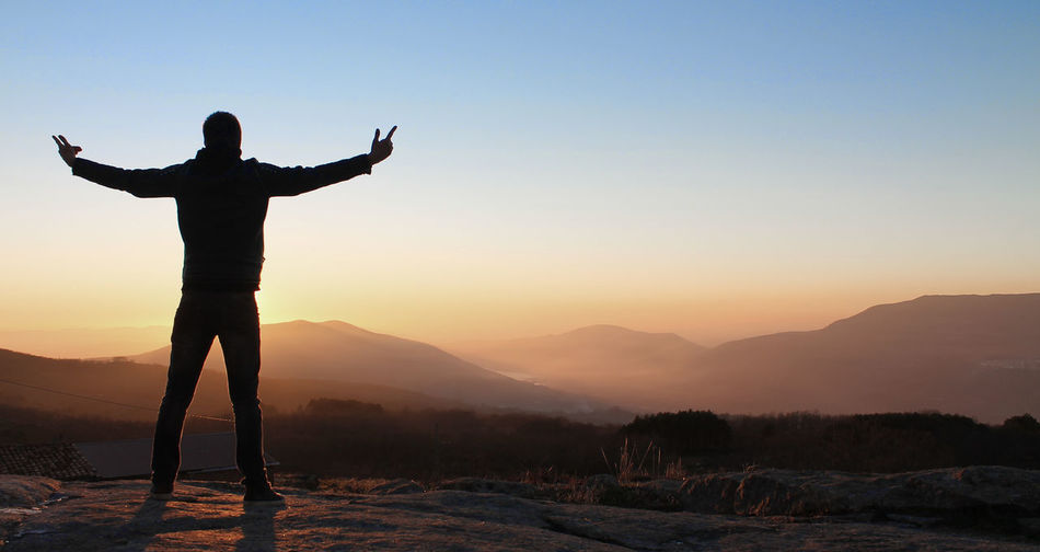 Full length of silhouette man with arms outstretched looking at mountains during sunrise