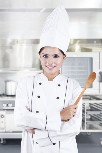 Portrait Of Smiling Chef Standing In Kitchen
