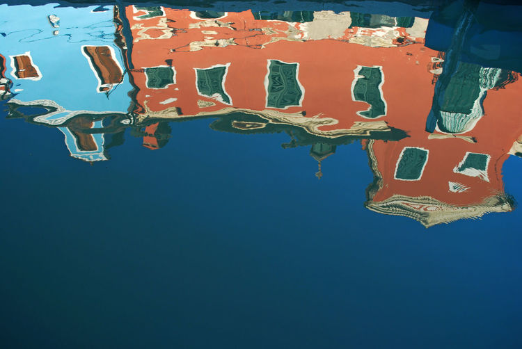 Low angle view of multi colored reflection on water against clear blue sky