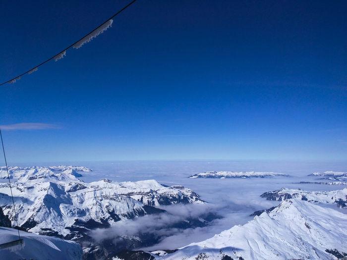 Aerial view of frozen landscape against blue sky