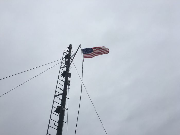 Low angle view of american flag by pole against sky
