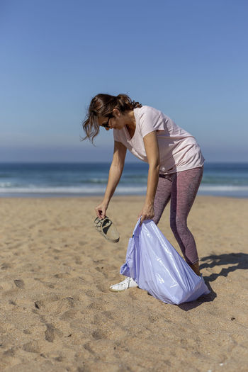 Woman with umbrella on beach against sea