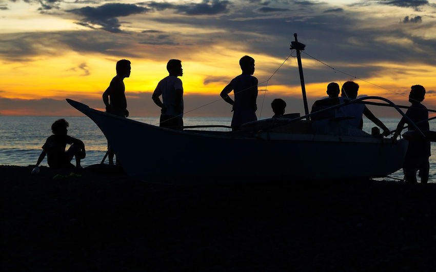 Silhouette people with boat at beach against sky during sunset