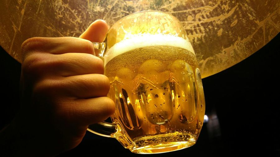 Close-up of hand holding beer glass