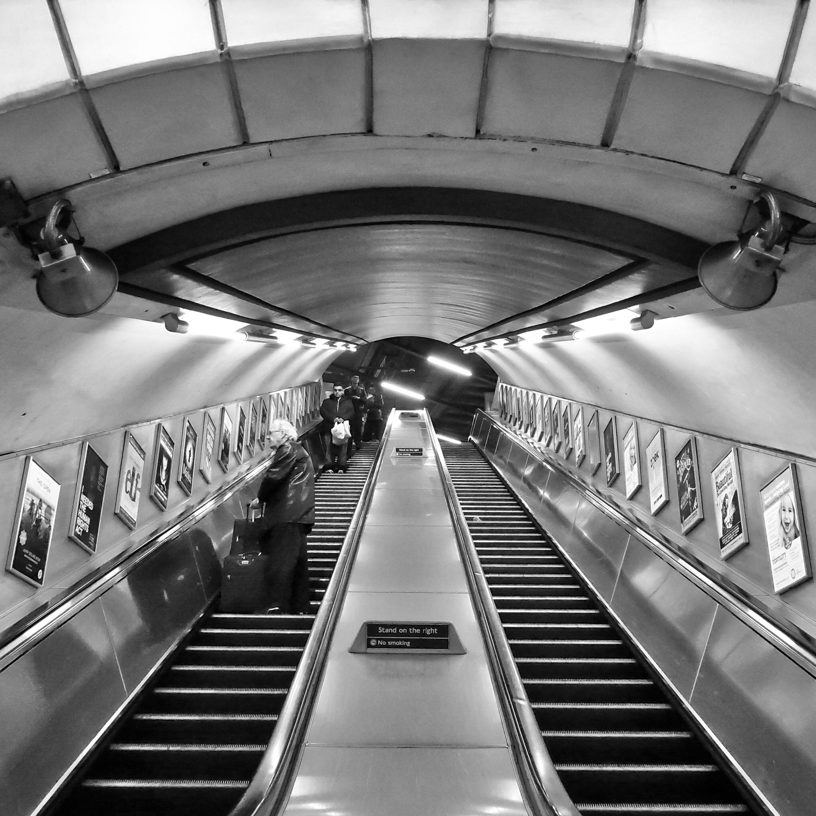 indoors, steps and staircases, escalator, ceiling, illuminated, steps, staircase, the way forward, railing, architecture, built structure, diminishing perspective, high angle view, modern, subway station, transportation, incidental people, vanishing point, technology, railroad station