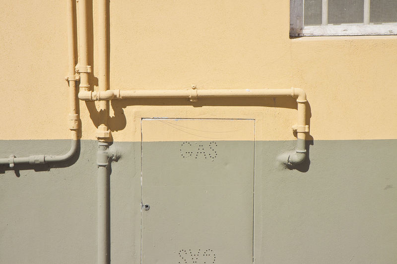 Gas pipes against a brick wall Brick Wall Gas Architecture Built Structure Close-up Closed Communication Connection Day Door Entrance Gas Pipe Gas Station Latch Metal Metal Pipe No People Outdoors Pipe - Tube Pipeline Safety Technology Text Wall - Building Feature