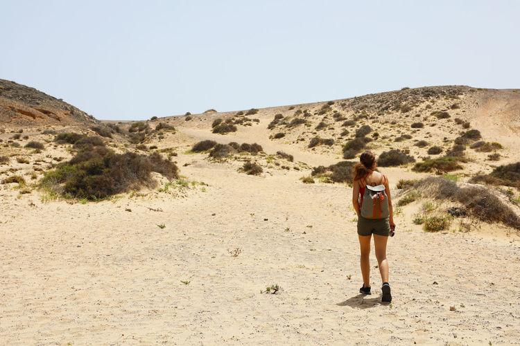 Rear View Of Woman Walking At Desert
