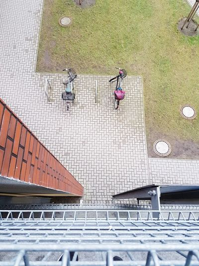 High angle view of parked bicycles on footpath in city