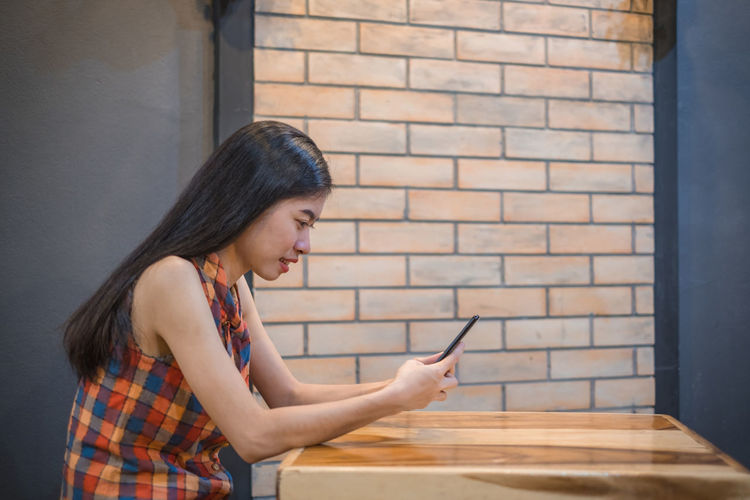 asian women sitting follow social news online with smartphone. he smile happily. Phone Mobile Woman Cell Asian  Females Telephone Young Girl Reading Shop Coffee Using Beautiful Use Sitting Smartphone Lifestyles People Business Leisure Technology person Text Communication Holding Banking News Texting Restaurant Hipster Modern Caucasian Travel Portrait Internet Fashion Indoor Smart Home Youth Watching Website Women One Person Young Adult Young Women Adult Connection Real People