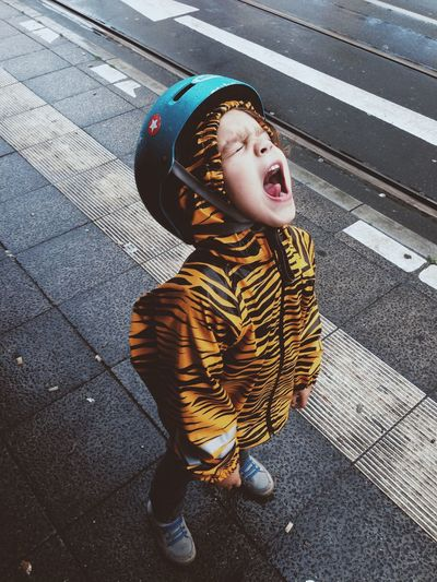 High angle view of boy in tiger print raincoat shouting on sidewalk