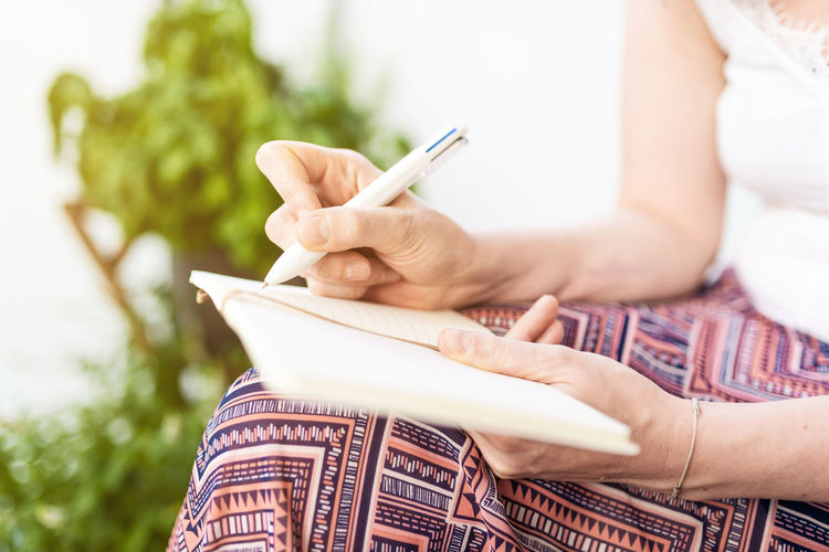 Midsection Of Mid Adult Woman Writing On Diary While Sitting In Park