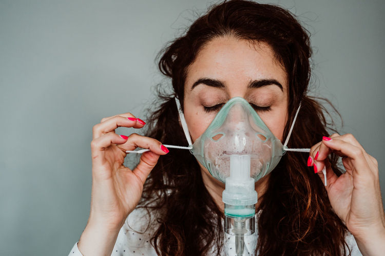 Close-up of woman wearing oxygen mask against gray background