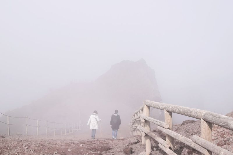 Rear view of people walking on mountain in foggy weather