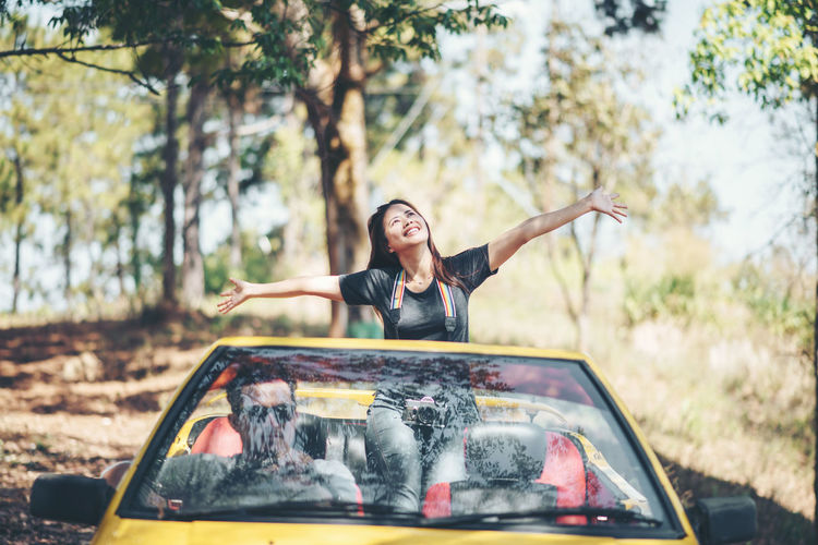Smiling Woman With Arms Outstretched Standing In Convertible Car