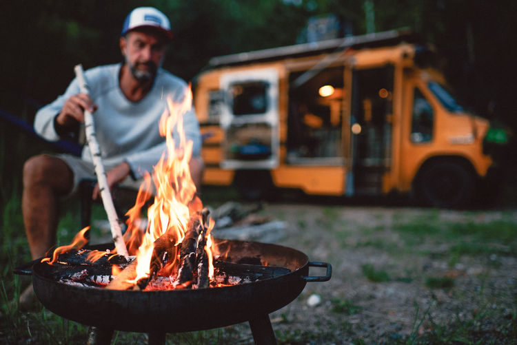 Man Burning Firewood In Fire Pit At Campsite