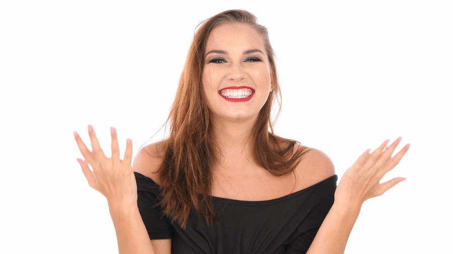 Studio Shot White Background Young Women Young Adult Indoors  Cut Out One Person Front View Women Portrait Casual Clothing Looking At Camera Beauty Copy Space Gesturing Standing Emotion Smiling Long Hair Hair Hairstyle Beautiful Woman Making A Face Teenager