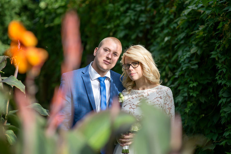 Portrait Of Bridal Couple Standing Amidst Plants At Park