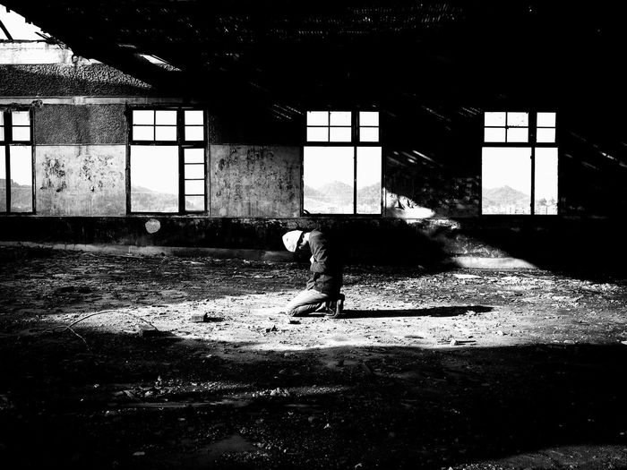 Side view of man standing in abandoned building