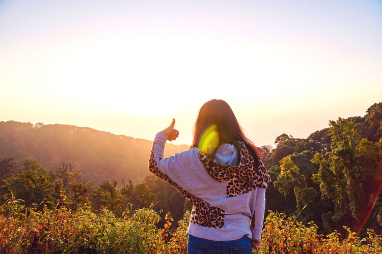 Rear view of woman showing thumbs up standing by plants against sky