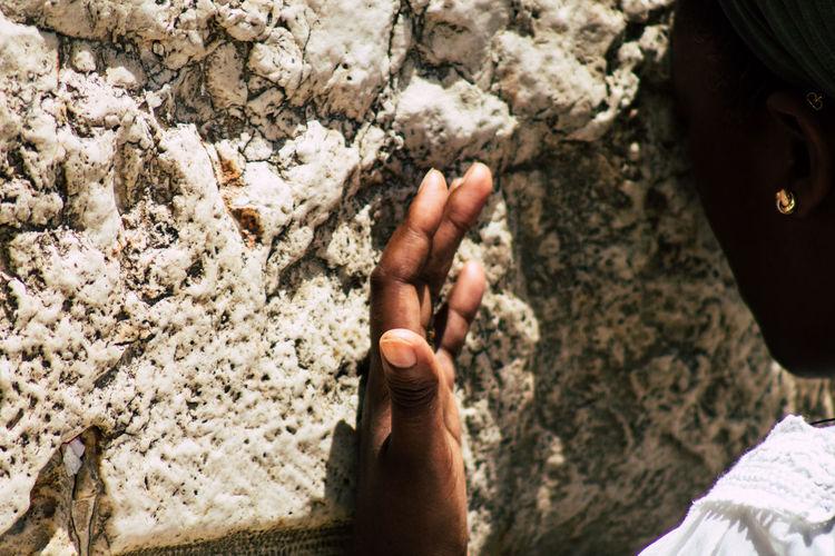 High angle view of man hand on rock