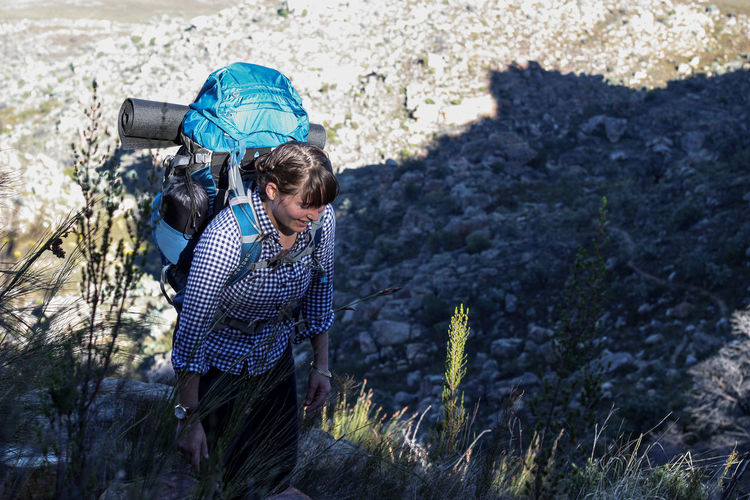Female hiker with backpack smiling while walking uphill Active Adventure Backpack Bag Day Explore Female Fit Happy Hike Hiker Hiking Leisure Activity Let's Go. Together. Mountain Nature Nature One Person Outdoor Photography Outdoors Shadow Summer Travel Walking Wilderness
