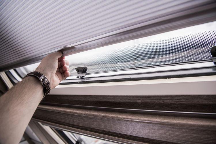 Cropped hand of man opening window in van