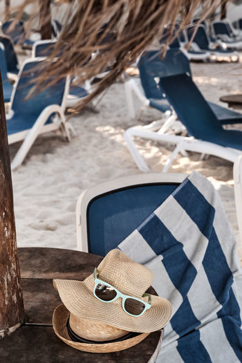 High Angle View Of Hats With Sunglasses On Table At Beach