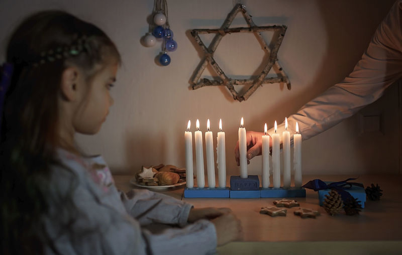 Cropped hand of mother lighting candles with cute girl at home