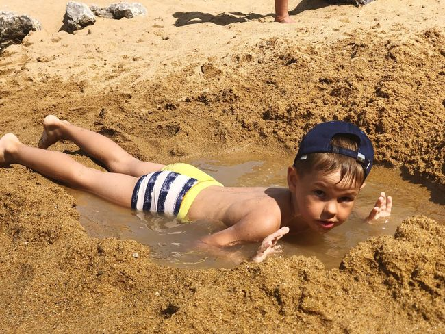 Sand Land Beach Real People Lifestyles Childhood Sunlight One Person Outdoors Vacations Males  Men Lying Down Boys Day High Angle View Leisure Activity Holiday Child Nature