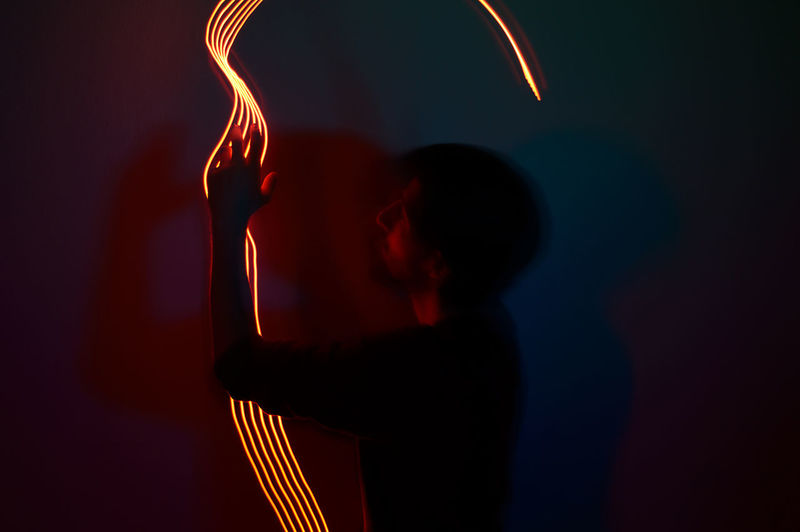 Midsection of man with illuminated light painting at night