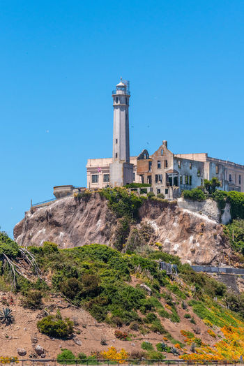 Alcatraz Built Structure Architecture Sky Building Exterior Blue Building Clear Sky Nature History The Past Tower Plant No People Copy Space Low Angle View Day Sunlight Land Travel Destinations Tree Guidance Lighthouse