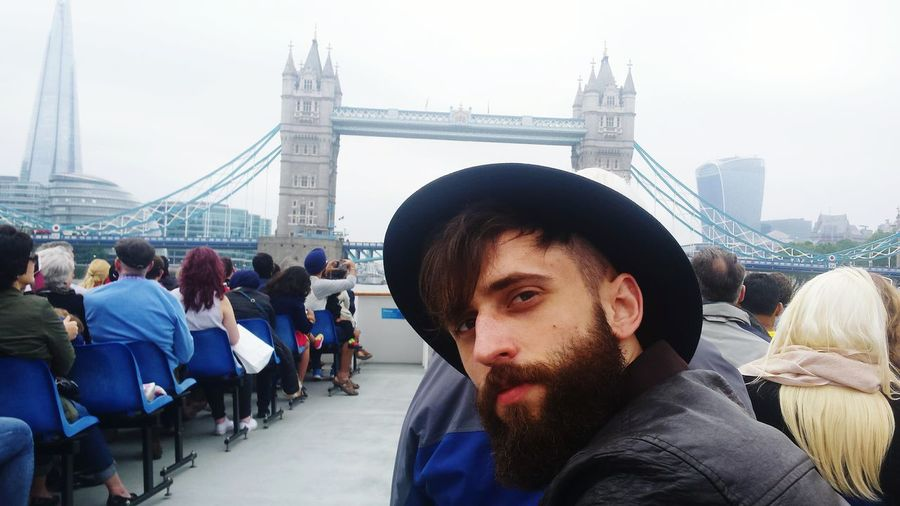 Portrait of bearded man on boat against tower bridge in city